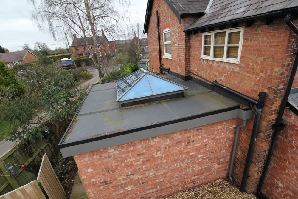 Aerial shot of orangery roof detail showing aluminium 44mm triple glazed roof lantern supplied in specified RAL colour by John Knight Glass and Firestone roof supplied and fitted by OPB Wirral builders.