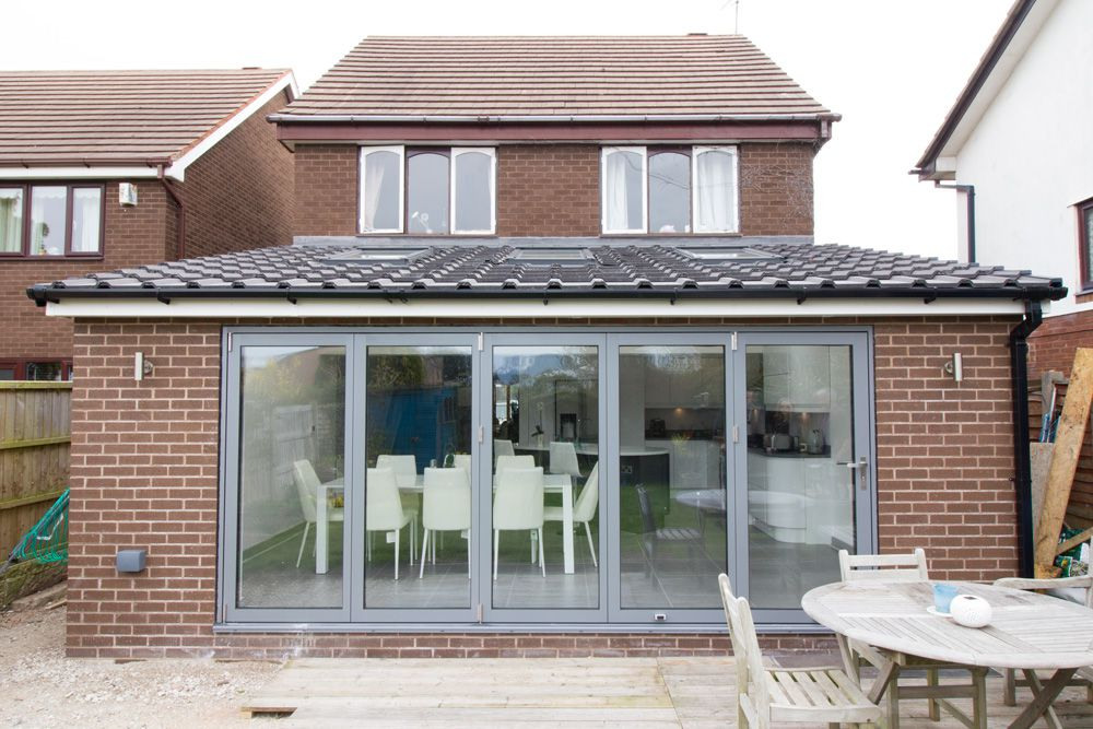 External shot of vaulted ceiling extension completed in Greasby, Wirral.  Velux roof lights and grey aluminium bi-fold doors have created a modern light filled open plan kitchen / living extension.