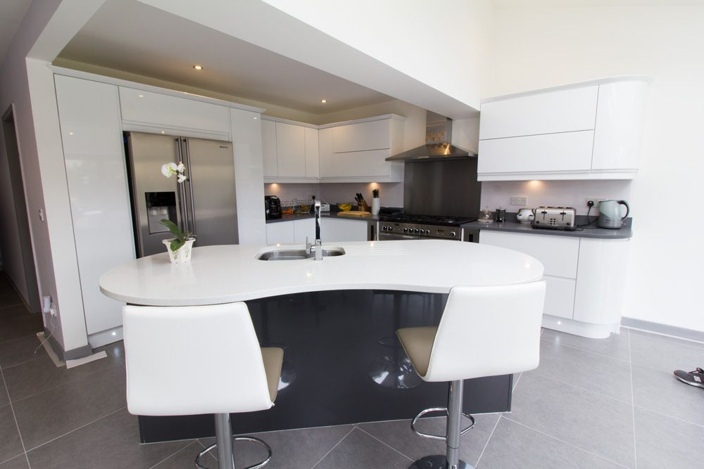 Bespoke kidney shaped kitchen island complete with stainless steel sink, taps and intergrated dishwasher.