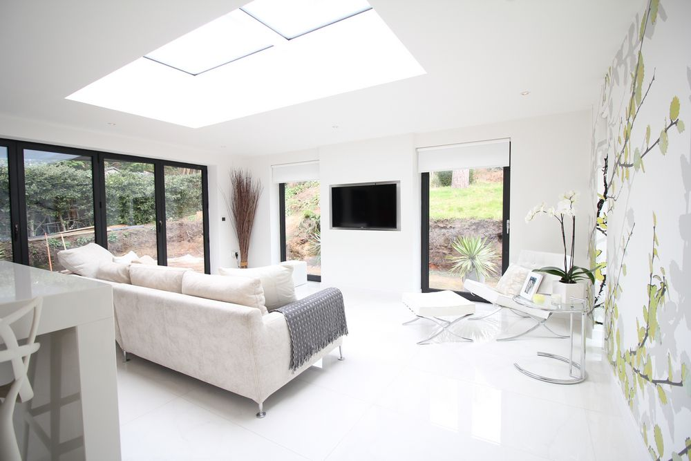 Internal shot of new rear extension created by OPB in Heswall, Wirral.  Picture show floor to ceiling aluminium windows and bi-fold doors complete with flat modern roof windows to create a light filled modern living area.