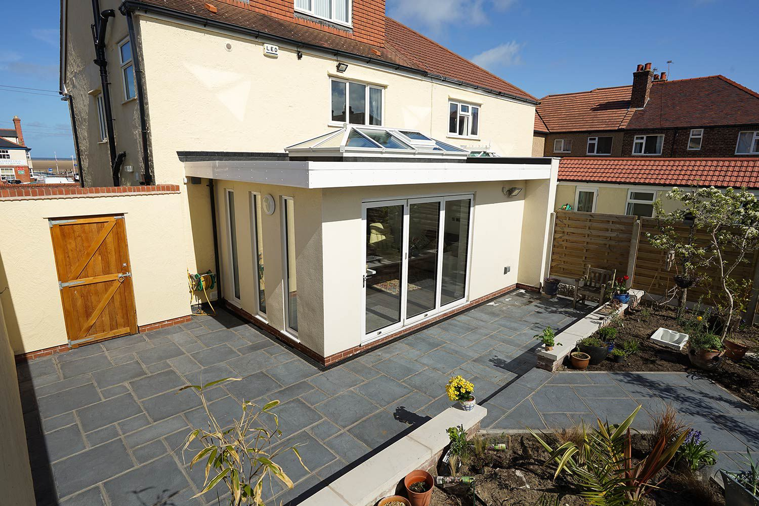 Modern orangery extension in Hoylake, Wirral.  Feauturing aluminium bi-fold doors, aluminium roof lantern and contemporary floor to ceiling windows supplied and installed by our partner John Knight Glass.
