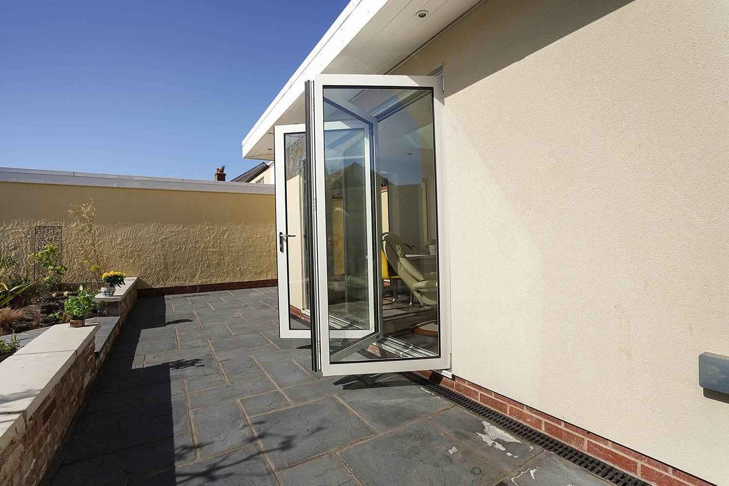 External shot of modern orangery extension showing floor to ceiling windows, bi-fold doors and external LED lighting in Hoylake, Wirral.