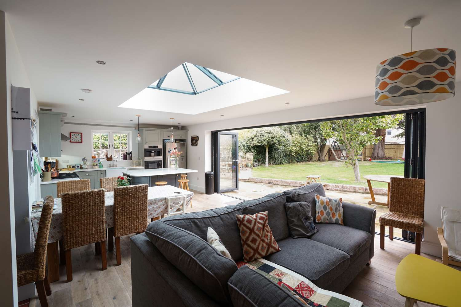 Interior shot showing the complete living area a space for cooking, dining, entertaining and living what more could you ask for this space has it all. Large bifold doors and a roof light allow for lots of natural light and easy access to outdoor entertaining.
