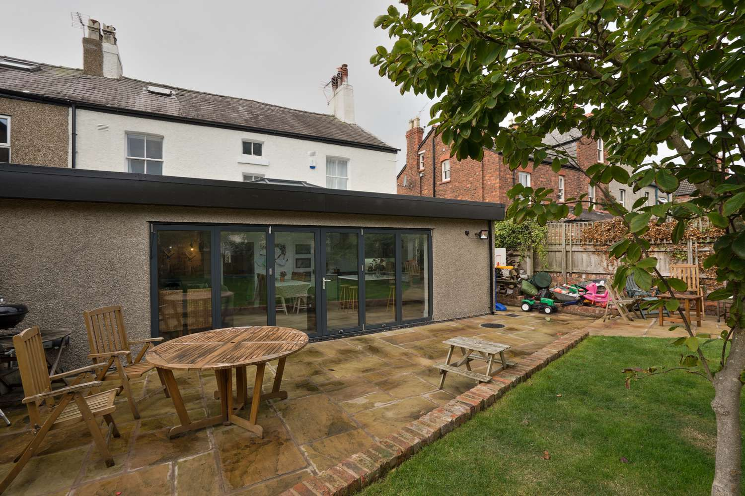 External picture showing large set of aluminium bifold doors on a completed orangery and groundworks.